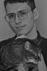 A picture of me (Aidan Malanoski) holding my cat (Rasputin, better known as Razz) in December 2019.